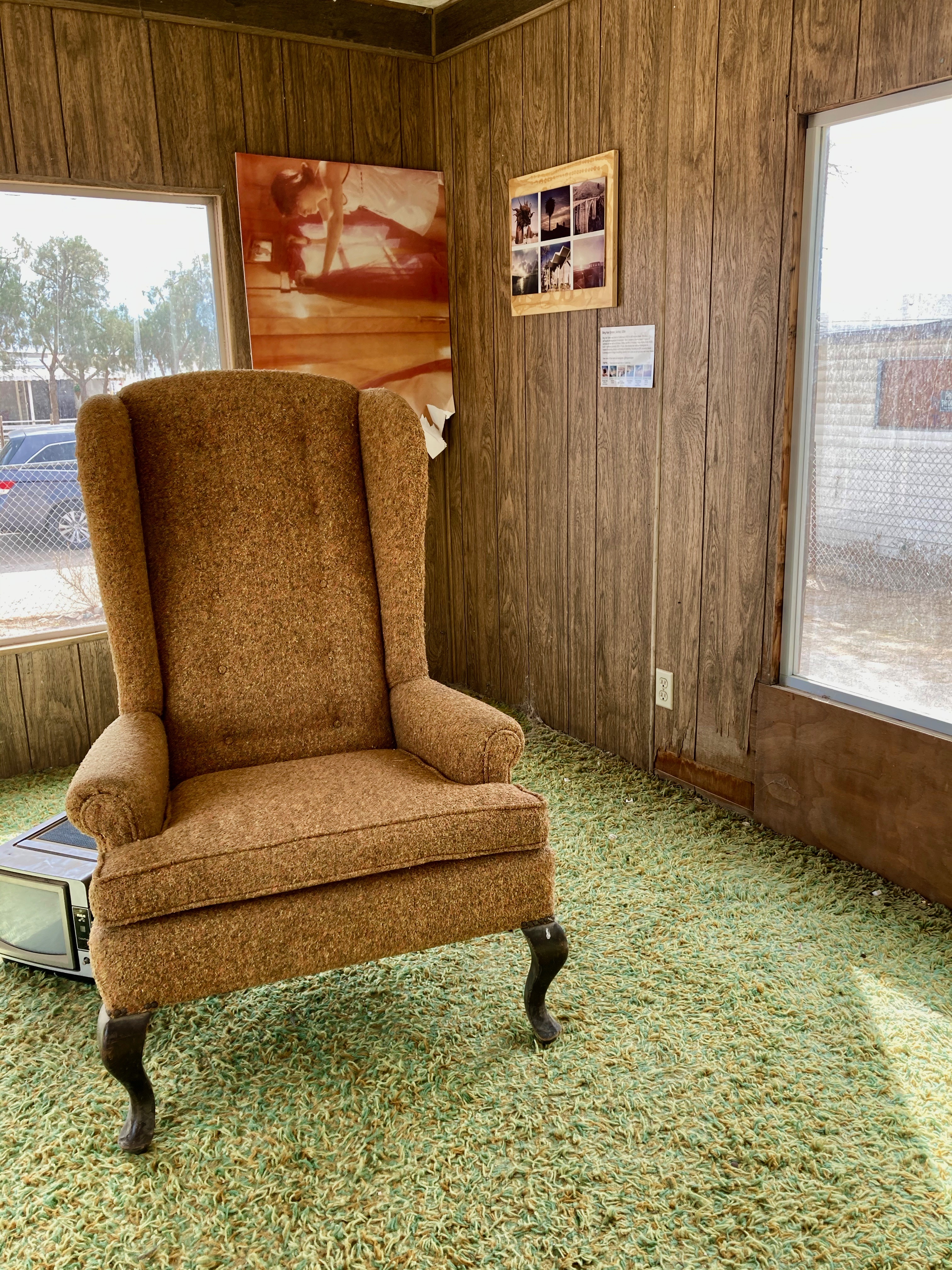domestic interior of old trailer with armchair, shag rug, and photographs on wood panelled walls