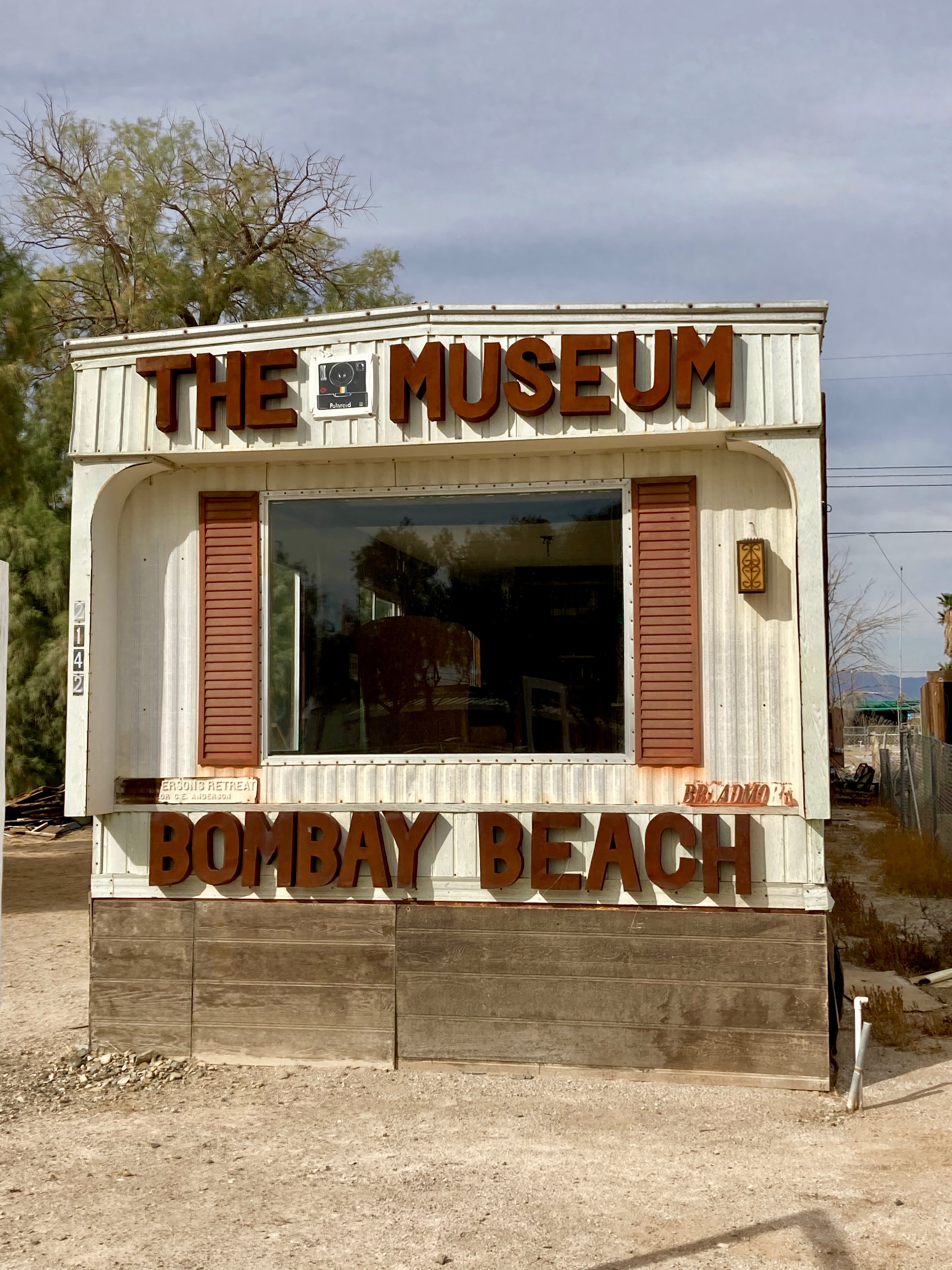exterior view of a white trailer labeled Museum Bombay Beach in large letters